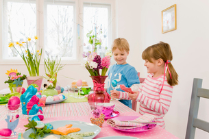 Girl and boy admire easter tableの写真素材 [FYI03488005]