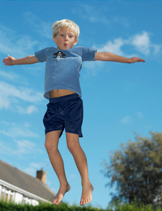Boy,7 playing on trampolineの写真素材 [FYI03488161]