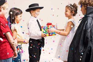 Child handing over present in partyの写真素材 [FYI03488207]