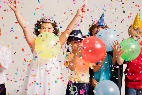 Party kids blowing balloonsの写真素材 [FYI03488208]