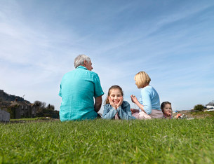 mature couple & children relax on grassの写真素材 [FYI03488404]