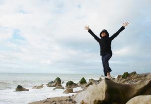 Girl spreading arms towards oceanの写真素材 [FYI03488470]