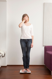 Woman standing on scaleの写真素材 [FYI03488508]