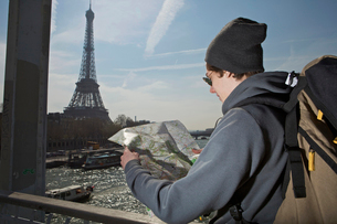 Man looking on the map near eiffel towerの写真素材 [FYI03488839]