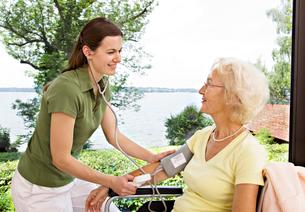 Nurse taking woman's blood pressureの写真素材 [FYI03489430]