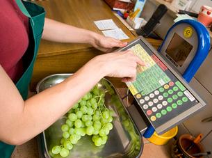 Shopkeeper putting fruit on scaleの写真素材 [FYI03489458]