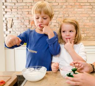 Girl,boy tasting baking ingredientsの写真素材 [FYI03489624]