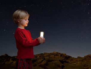 Boy with energy saving light bulbの写真素材 [FYI03490026]