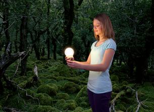 Girl with energy saving light bulbの写真素材 [FYI03490116]