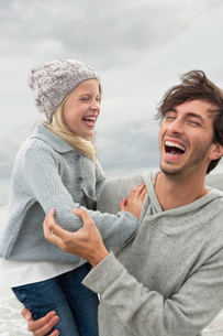 Father and daughter laughing on beachの写真素材 [FYI03491107]