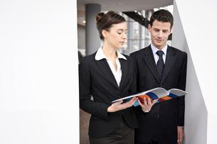Business people looking at brochureの写真素材 [FYI03491174]