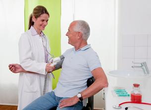 Doctor  patient's taking blood pressureの写真素材 [FYI03491352]