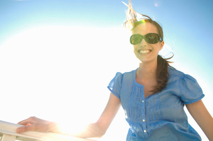 Chic woman in sunlight looks to cameraの写真素材 [FYI03491996]