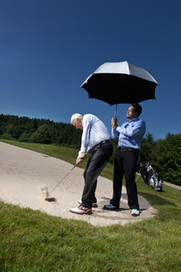 Caddy is holding a parasol over a golferの写真素材 [FYI03492093]