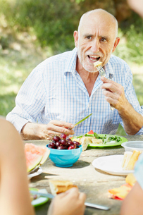 Older man eating at picnic tableの写真素材 [FYI03492221]