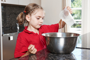 Girl pouring water in to mixing bowlの写真素材 [FYI03492338]