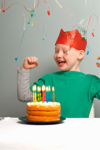 Young boy with cake,party hat,streamerの写真素材 [FYI03492740]
