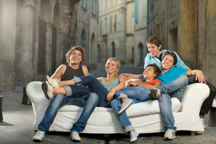 Group relax on couch laughing in streetの写真素材 [FYI03492947]