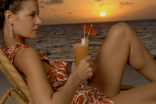 Woman drinking cocktail on beachの写真素材 [FYI03492973]