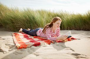 Teenager reading book in sand dunesの写真素材 [FYI03492988]