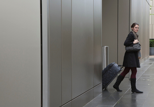 Woman pulling bag on wheelsの写真素材 [FYI03492996]