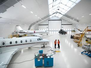 Engineers in jet aircraft hangarの写真素材 [FYI03493454]