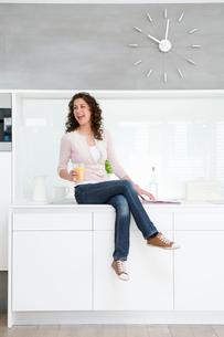 Woman sitting on kitchenetteの写真素材 [FYI03493525]