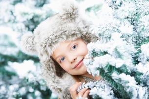 Girl standing between snowy treesの写真素材 [FYI03493773]