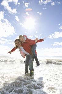 Mom and daughter at beach piggyback rideの写真素材 [FYI03493845]