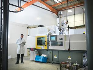 Scientist with plastic moulding machineの写真素材 [FYI03494078]