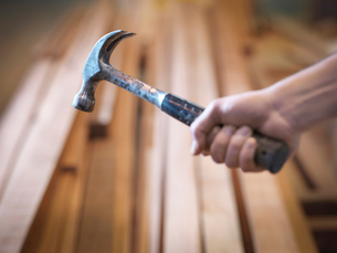 Hand holding hammer next to timberの写真素材 [FYI03494159]