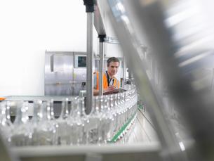 Factory worker examining bottlesの写真素材 [FYI03494195]