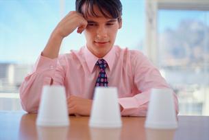 Businessman examining cups in officeの写真素材 [FYI03494216]