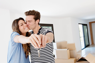 Kissing couple with keys to new homeの写真素材 [FYI03494231]