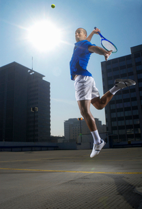 Tennis player jumping on rooftop courtの写真素材 [FYI03494485]