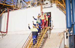 Workers waving from steps of oil rigの写真素材 [FYI03494651]