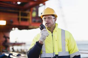 Worker using walkie talkie on oil rigの写真素材 [FYI03494652]