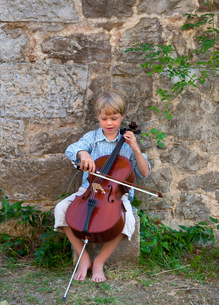 Boy playing cello outdoorsの写真素材 [FYI03494686]