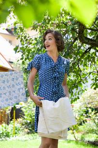 Woman folding sheet on clotheslineの写真素材 [FYI03494847]