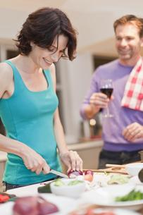 Woman cooking dinner in kitchenの写真素材 [FYI03495111]