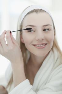 Smiling woman applying makeupの写真素材 [FYI03495214]