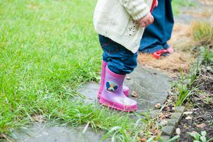 Toddler girl wearing pink rainbootsの写真素材 [FYI03495299]