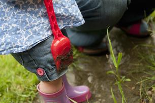 Toddler girl holding dirty shovelの写真素材 [FYI03495312]