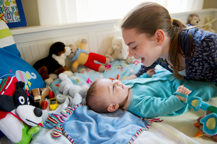 Girl playing with baby brother on bedの写真素材 [FYI03495726]