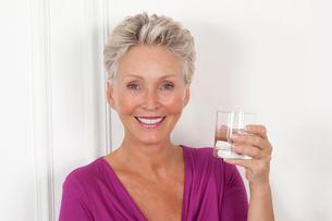 Older woman having glass of waterの写真素材 [FYI03495809]