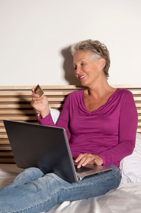 Older woman shopping online on bedの写真素材 [FYI03495818]