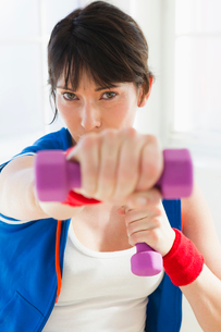 Woman lifting weights indoorsの写真素材 [FYI03495849]