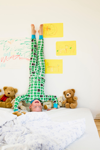 Boy doing headstand on bedの写真素材 [FYI03495868]