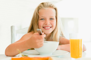 Girl eating cereal at breakfast tableの写真素材 [FYI03495914]