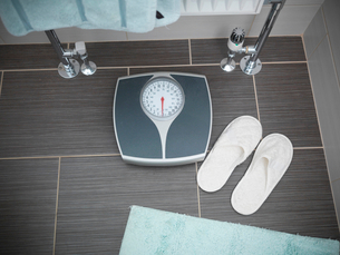 Slippers and weighing scale in bathroomの写真素材 [FYI03496184]